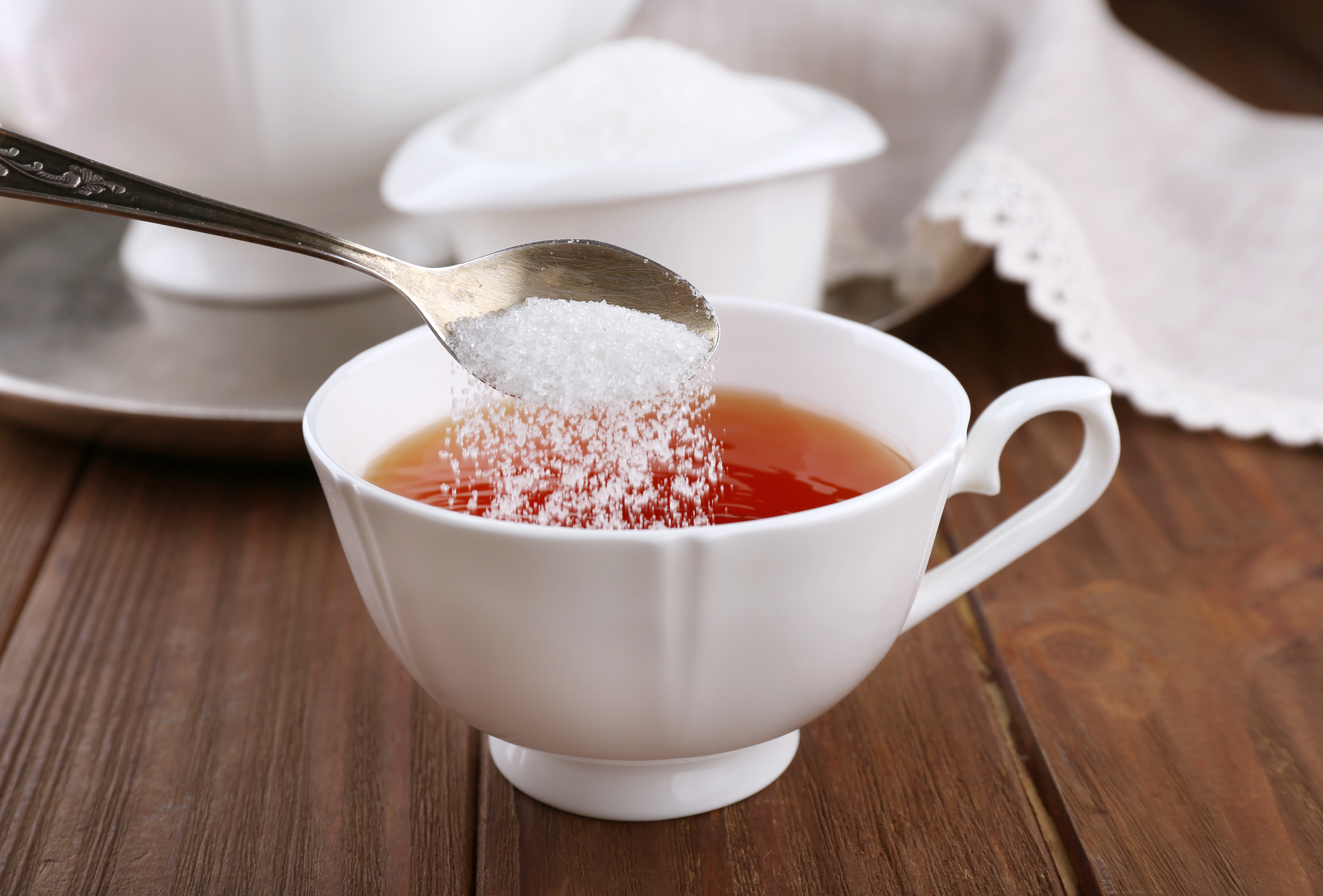 Adding sugar to cup of black tea on wooden table
